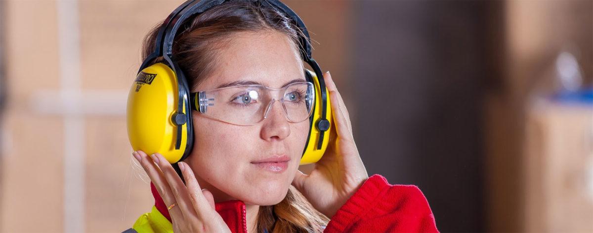 Eine Alleinarbeiterin mit Schutzbrille und Gehörschutz als ein Beispiel für Alleinarbeiterschutz